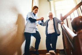 Caregiver helping senior woman down stairs