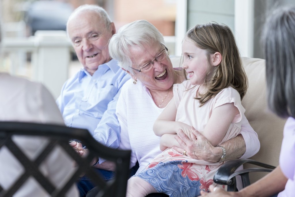Happy senior woman laughs while enjoying spending time with her adorable young granddaughter.