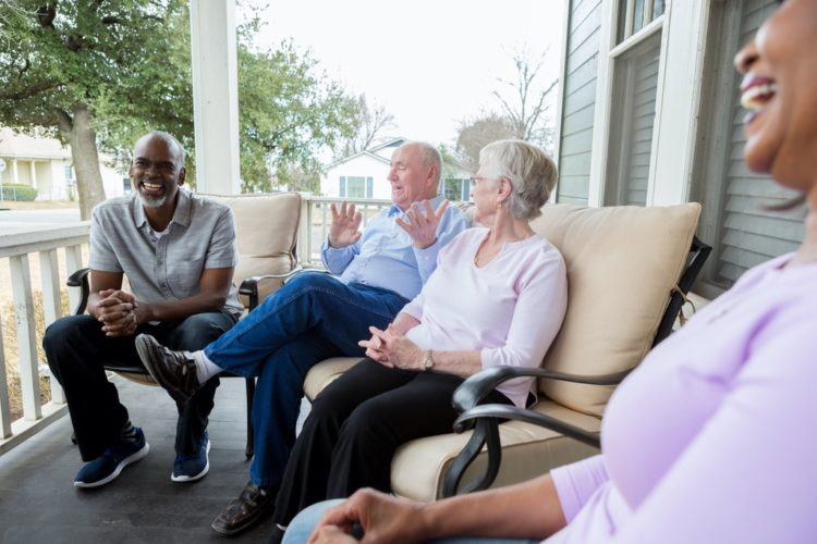 Four seniors enjoy one another's company while sitting on a porch together.